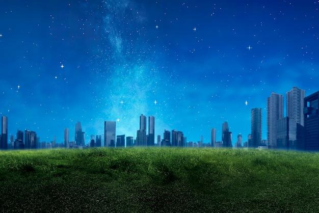 高層ビルと緑の牧草地と夜景の背景を持つモダンな建物