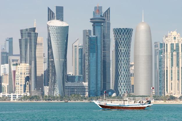 Небоскребы в центре города с водой и лодкой на переднем плане дохи, катар.