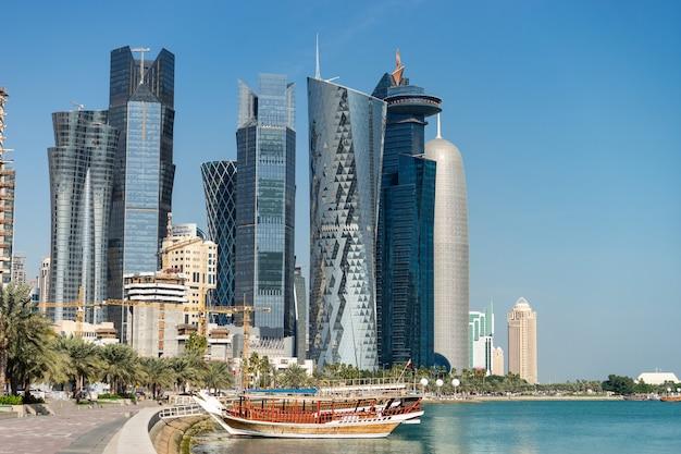 カタールのドーハの水とボートの前景がある市内中心部の高層ビル。