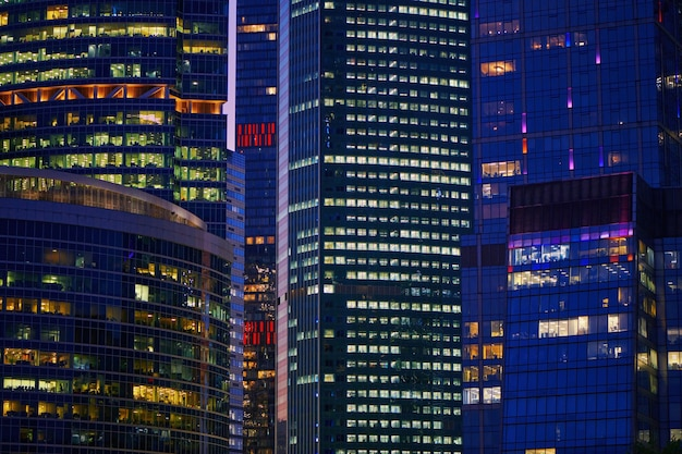 Skyscrapers windows of moscow-city downtown business center with tall buildings at night. illuminated windows of business office center. late night overtime in a modern office building.