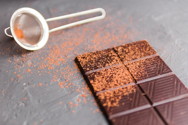 Slab of chocolate with cocoa next to strainer