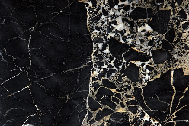 A slab of dark expensive marble with yellow streaks, called new portoro.