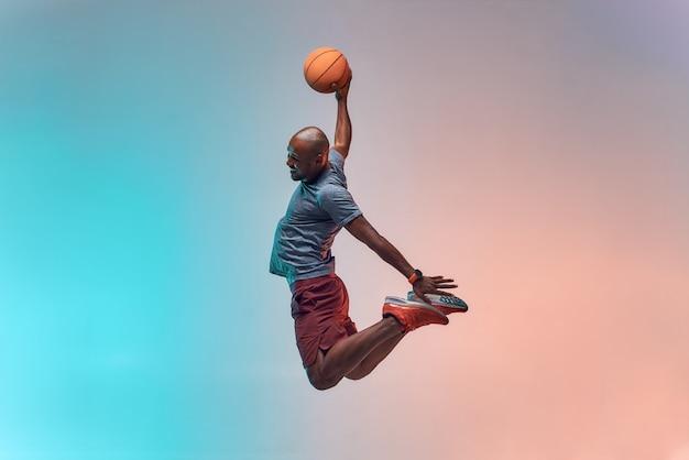 Слэм данк в полный рост молодого африканского игрока в баскетбол, прыгающего на красочном фоне