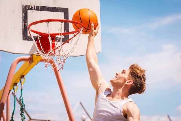 슬램 덩크. 슬램 덩크를 만드는 젊은 농구 선수의 측면보기