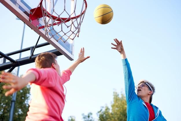 슬램 덩크. 젊은 백인 농구 선수, 농구 후프에 공을 던지는 소년