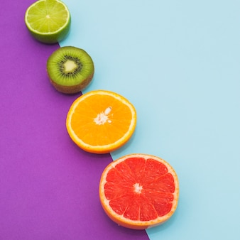 Slanting row of citrus fruits and kiwi on dual blue and purple background