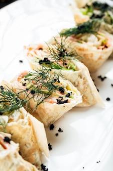 Slapjack rolls with salmon black caviar and dill