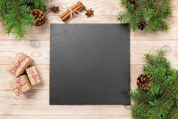Slate blackboard on wooden table with christmas decoration, black slate stone on wooden , , new year concept