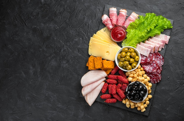 Slate board with slicing of different sausages and cheese. top view with copy space.
