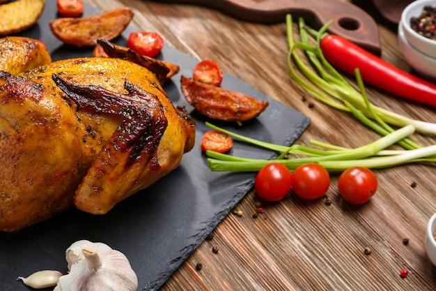 Грифельная тарелка с жареным пивом может курица на деревянной поверхности