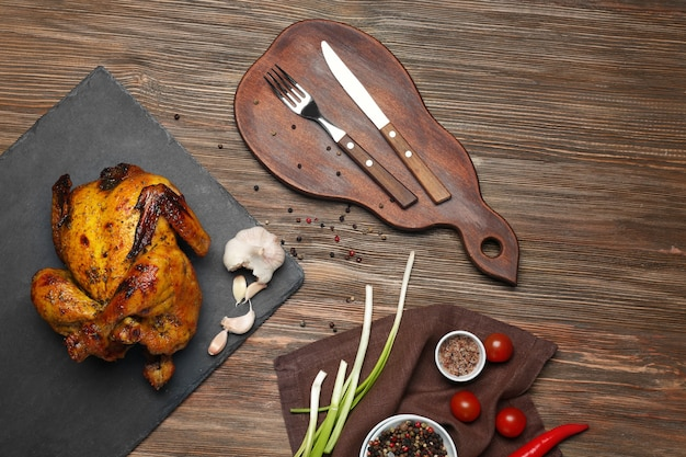 Грифельная тарелка с жареным пивом может курица на деревянном столе