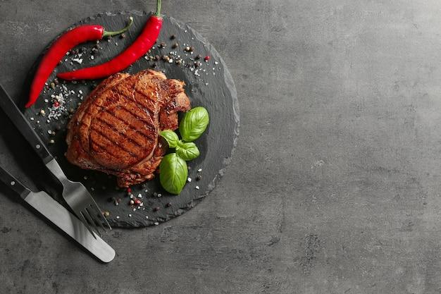 グレーのスペースに美味しいグリルステーキとスパイスを添えたスレートプレート