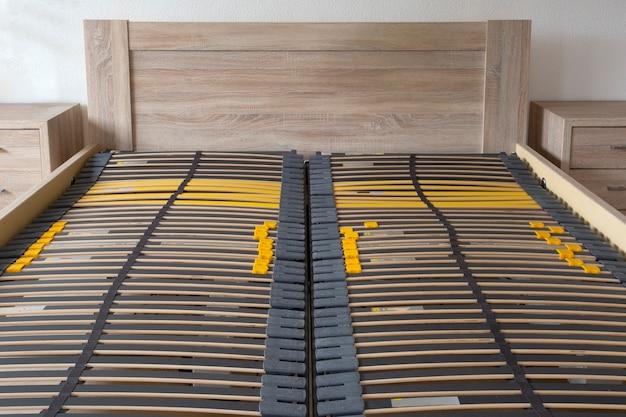 Slatted base wooden element double bed frame close up in bedroom