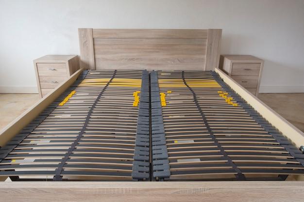 슬레이트 베이스 나무 요소 더블 침대 프레임이 침실에서 닫힙니다.