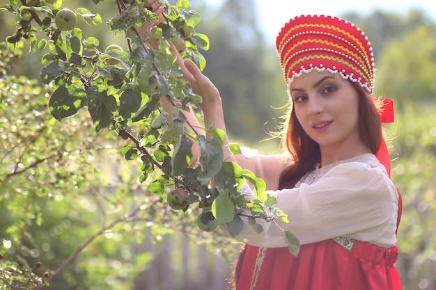 Славянин в традиционной одежде собирает урожай яблок