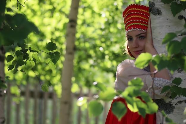 Славянин в традиционной одежде прячется за деревьями