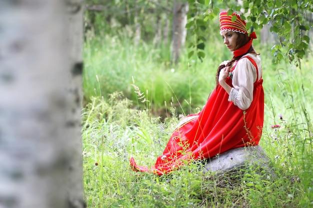 전통 의상을 입은 슬라브가 자연 속에 앉아 있다
