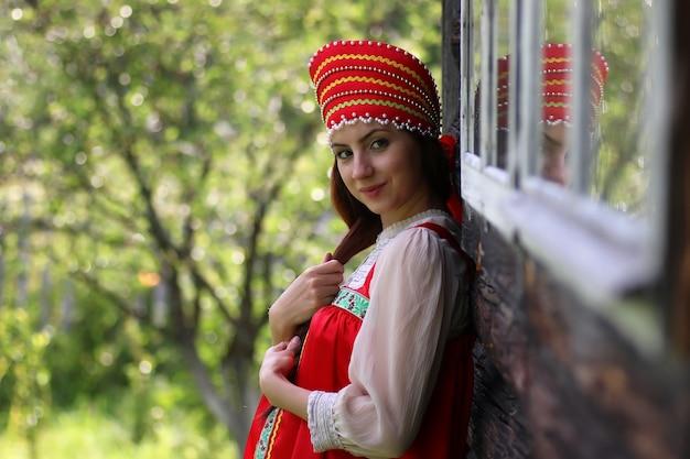 Славянка в традиционной одежде на деревянной стене