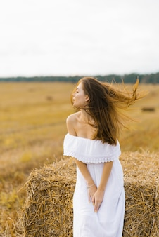 Slavic girl with long blond hair in a white dress standing in a field with bales of straw, her hair blowing in the wind