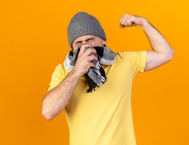 모자와 스카프를 착용하는 슬라브 남자는 목에 손을 넣습니다.