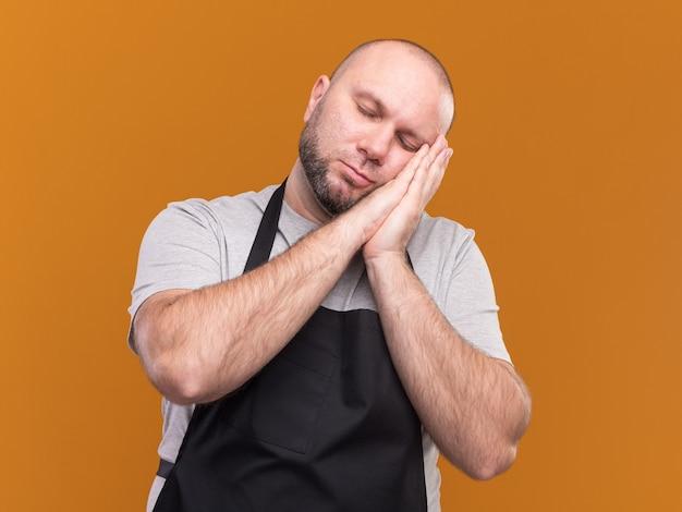 주황색 벽에 고립 된 수면 제스처를 보여주는 제복을 입은 닫힌 눈을 가진 슬라브 중년 남성 이발사