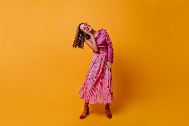オレンジ色の壁のポーズで動く暗い短い髪のスラブモデル。濃いピンクの外観の非常に美しい女性
