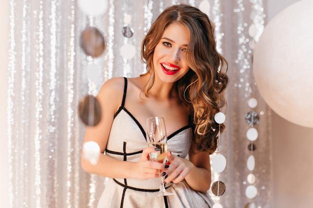 곱슬 긴 머리와 붉은 입술을 가진 슬라브 여성은 밝은 빛에 서서 새해를 기뻐하며 맛있는 샴페인을 마신다. 밝고 빛나는 방에서 파티에서 2019를 축하하는 여자의 초상화