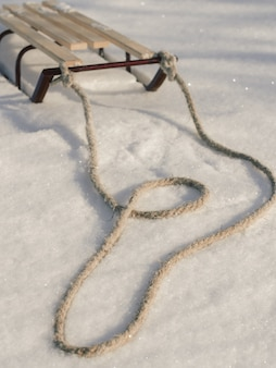 Санки с веревкой в снегу зимой крупным планом.