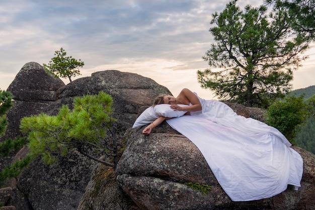 Выспитесь и отдохните в живописном месте на природе. молодая женщина спит среди гор, деревьев на чистой белой простыне. кровать под голубым небом и комфорт в путешествии, тяга к природе