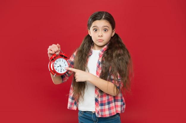 수면시간. 어린이 일정. 각성. 시계에 시간을 보여주는 십 대 아이. 손가락을 가리키는 소녀. 늦는 아이. 좋은 아침이에요. 시간 관리. 레트로 기계식 시계.
