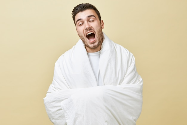 Sleep deprivation and insomnia concept. portrait of young man with slumberous eyelids yawning with mouth wide opened posing isolated wrapped in white blanket, feeling sleepy because of early awakening