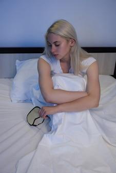 수면 장애, 불면증. 잠 옷을 입은 침대에 앉아 우울증으로 고통받는 여성-이미지