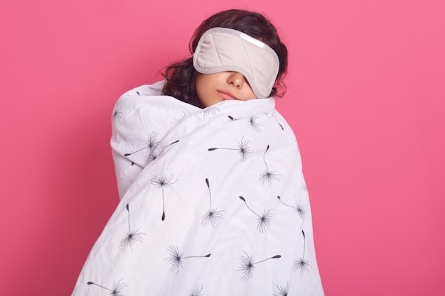 Sleep equipment concept. portrait of brunette woman wrapped white blanket and wearing sleeping eye mask. studio shot of young female isolated on pink, lady being ready to fall asleep.
