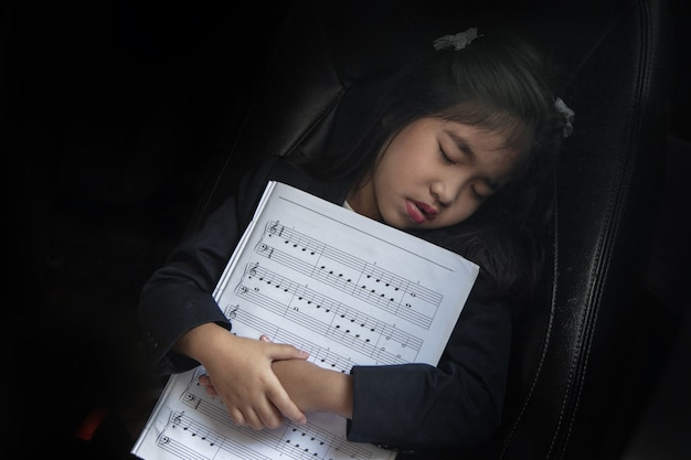 Sleep kid with music note on seat car as love music
