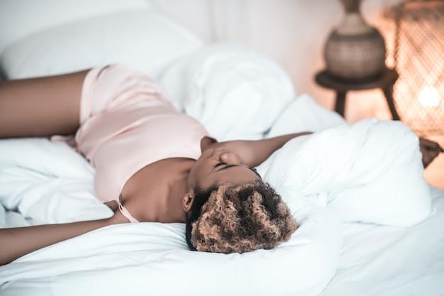 Спи как младенец. темнокожая молодая взрослая женщина в легкой пижаме спит, раскинув руки в стороны, лежа на спине