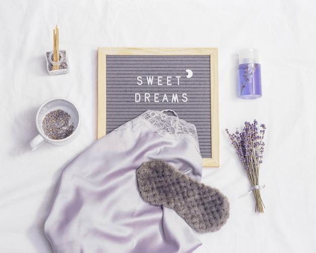 수면 마스크, 실크 잠옷, 아로마 봉선화, 흰색 침구에 마른 라벤더 꽃. 당신에게 달콤한 꿈을 기원합니다.