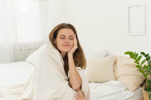 수면 문제, 불면증. 눈을 감고 담요를 쓴 피곤한 젊은 여성은 침대에 앉아 잠을 잔다. 여성이 일어나서 침대에서 일어나는 것은 어렵습니다.