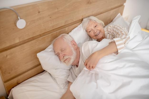 睡眠。一緒にベッドに横たわっている老人と女性