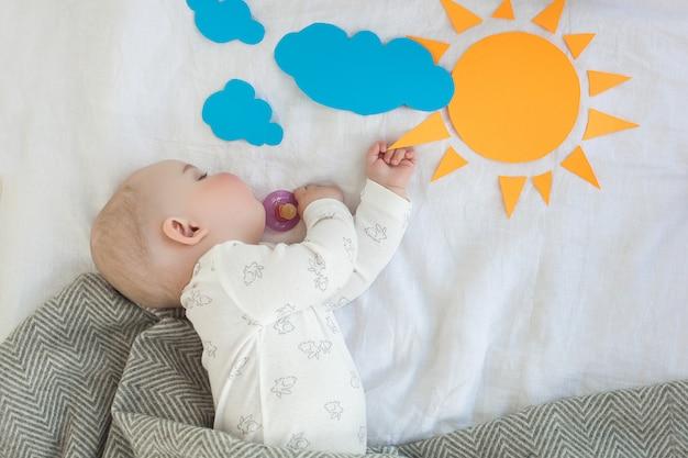 Спящего ребенка в постели по утрам. время просыпаться. утреннее солнце. младенец сонный. маленький ребенок спит. Premium Фотографии