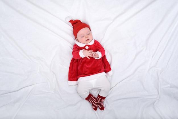 Sleeping baby in santa costume
