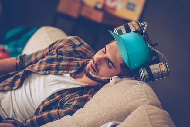 잠자는 숲속의 미녀. 지저분한 방에 있는 소파에서 낮잠을 자는 맥주 모자를 쓴 잘생긴 청년의 클로즈업