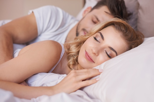 Sleeping couple in comfortable bed