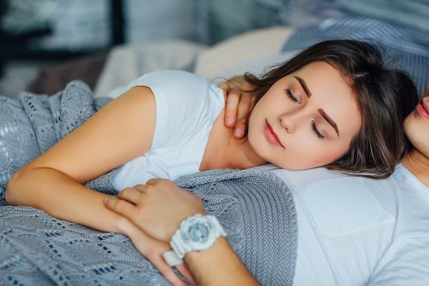 快適なベッドで寝ているカップル、彼女の男と横臥の女の子