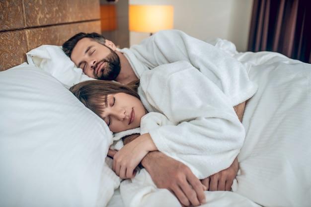 Спать. пара в белых халатах спит и выглядит мирно