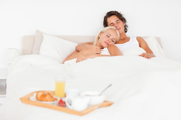 Sleeping couple with the breakfast put on a tray