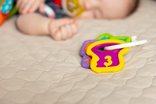おもちゃで眠っているかわいい赤ちゃん、生後3ヶ月。セレクティブフォーカス。 Premium写真