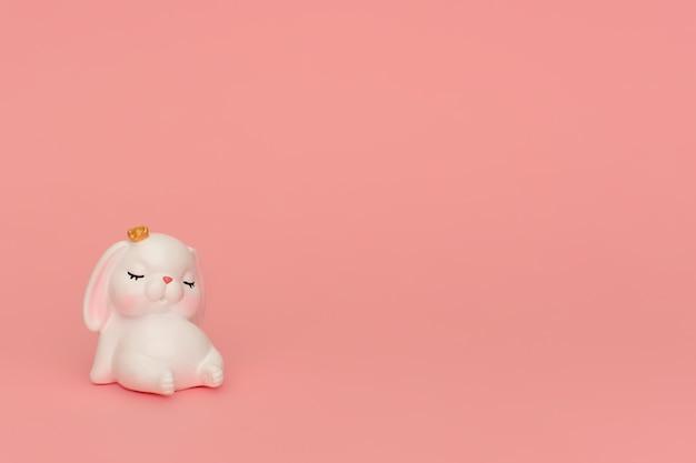 ピンクの背景の王冠でかわいいウサギを眠っています。ピンクの壁に座っているピンクの耳を持つ白いマスコットグッズ眠そうなウサギ