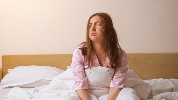 우아한 분홍색 잠옷을 입고 잠자는 검은 머리 여성이 킹 사이즈 침대에 빠르게 앉아 침실 클로즈업에서 흰 벽에 대한 불만을 표현합니다