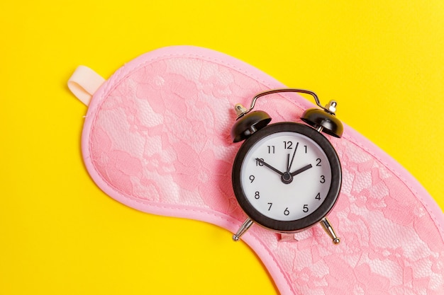 Sleeping eye mask, alarm clock isolated on yellow table