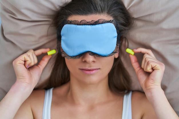 Спящая женщина, используя маску для глаз и затычки для ушей для лучшего сна, защиты от шума и сладких снов